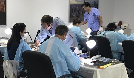 dental students in classroom performing hands-on exercises with instructor